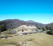 Mountain Farm With Fenced Pasture And Trout Stream Running Through